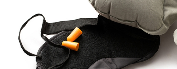 An eye mask and ear plugs will help get you off to sleep on the plane